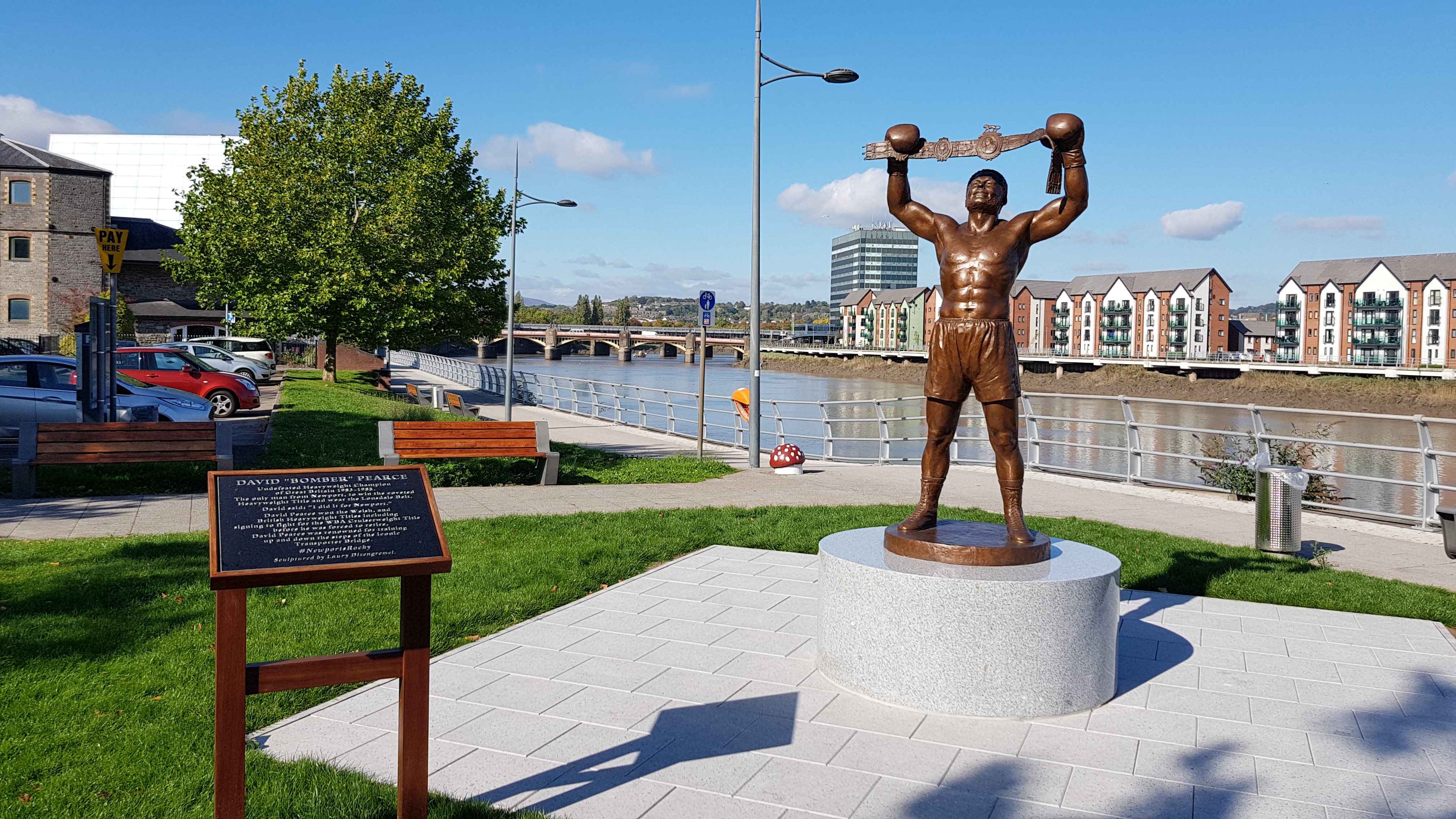 Bronze Sculpture of David 'Bomber' Pearce holding his belt aloft by Laury Dizengreme against blue skies
