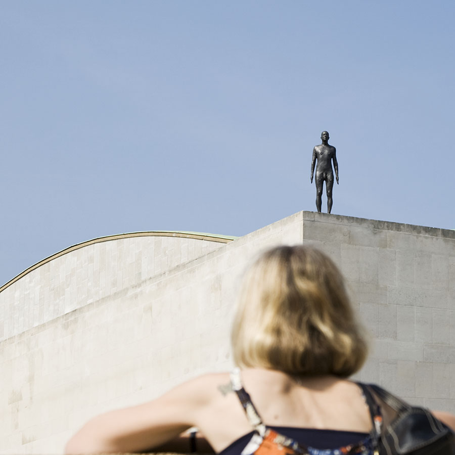 A woman looks up at 1 of 31 actual size figures on London's skyline in Event Horizon, perched on the top of a building