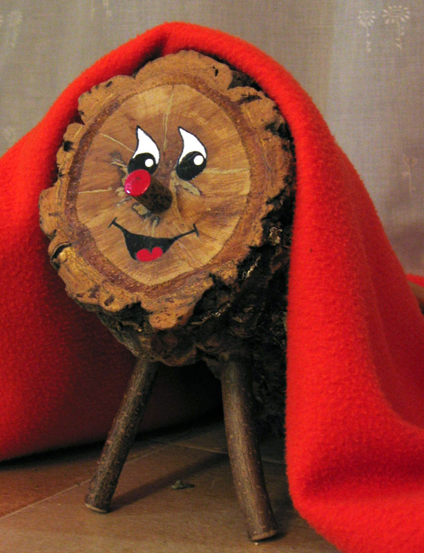 Caga Tió - a log with a smiley face beneath a red blanket