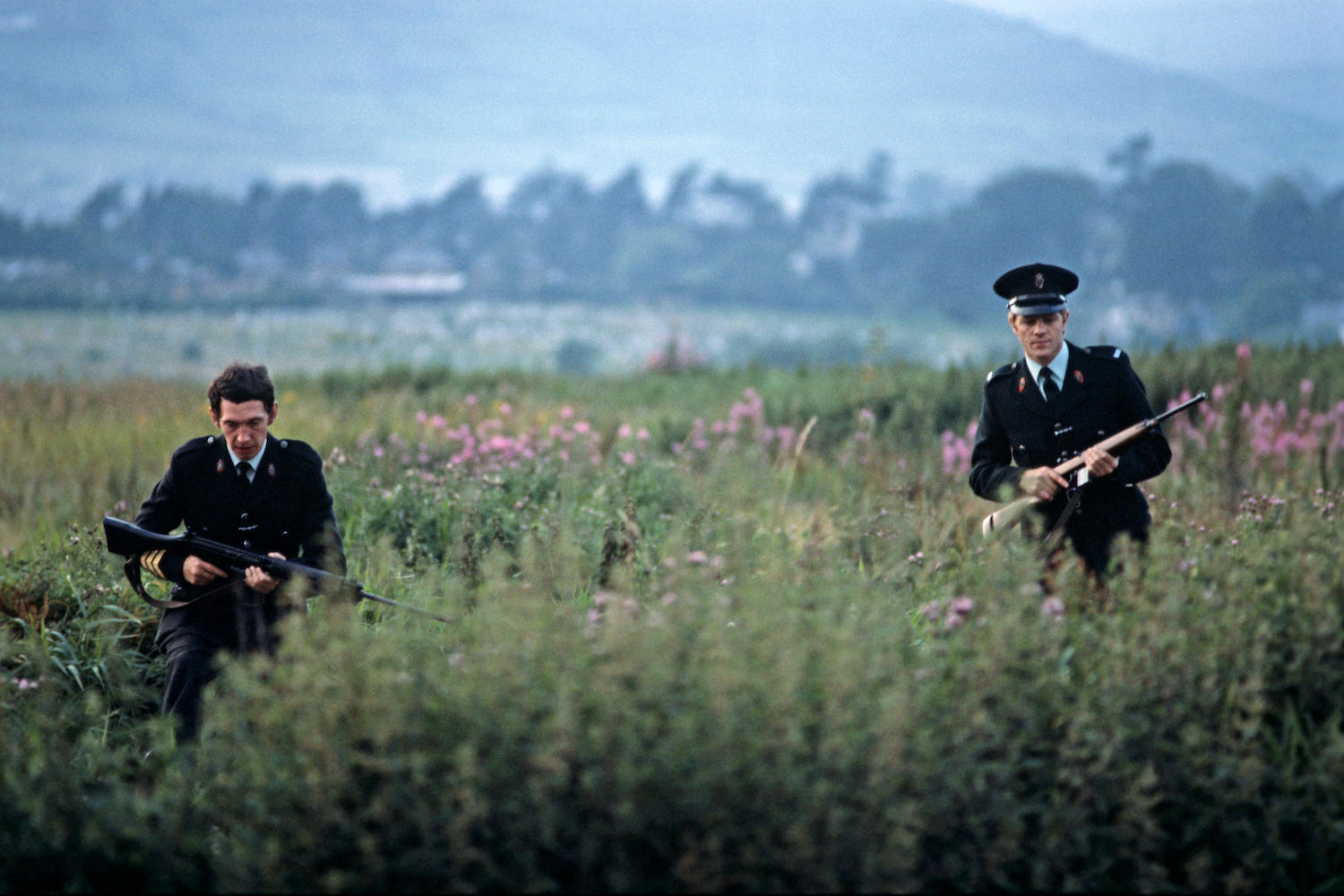Royal Ulster  Constabulary policemen search for weapons and ammuninition in wasteland during the Troubles