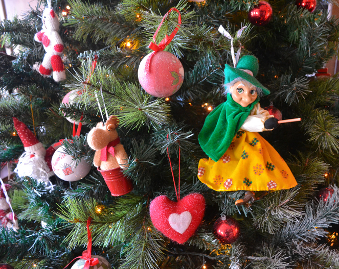 Befana ornament hangs from a christmas tree