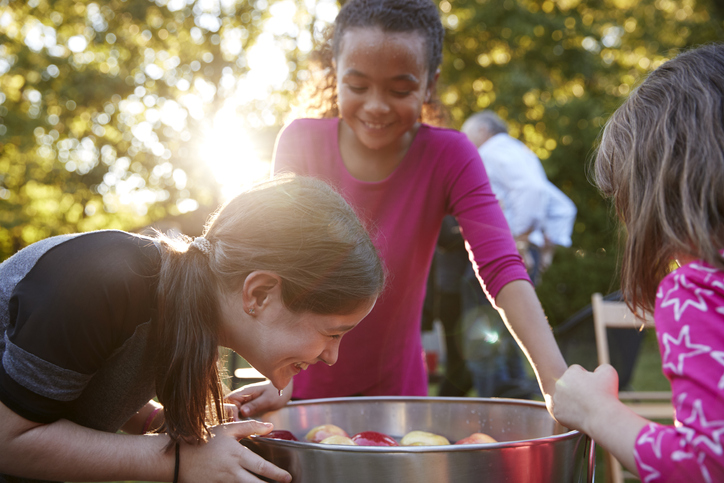 girls laugh while apple bobbing in the sunshine