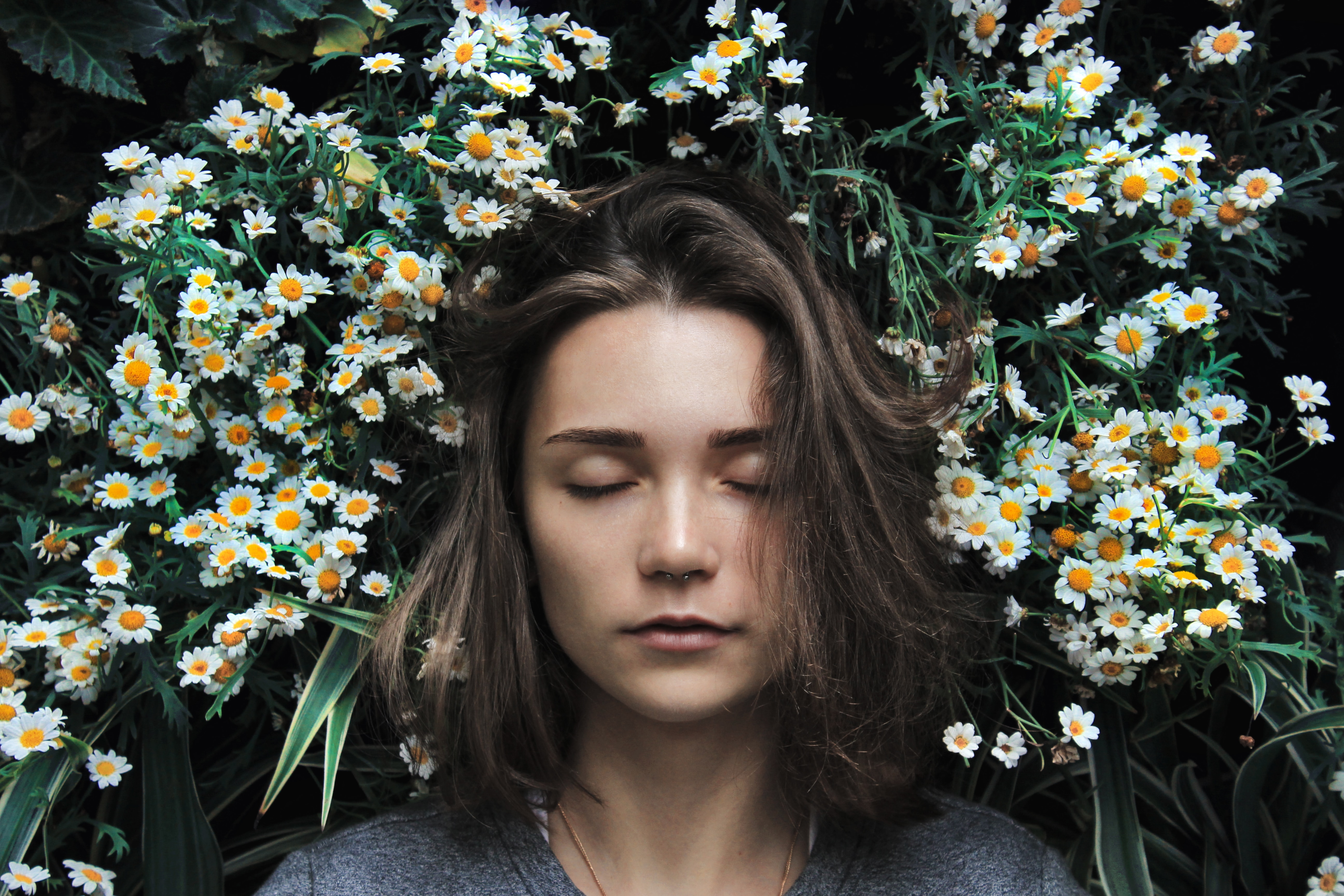 woman dreaming in a field of daisies