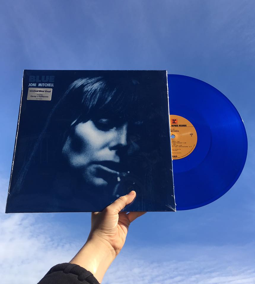 Joni Mitchell blue album held up against the sky
