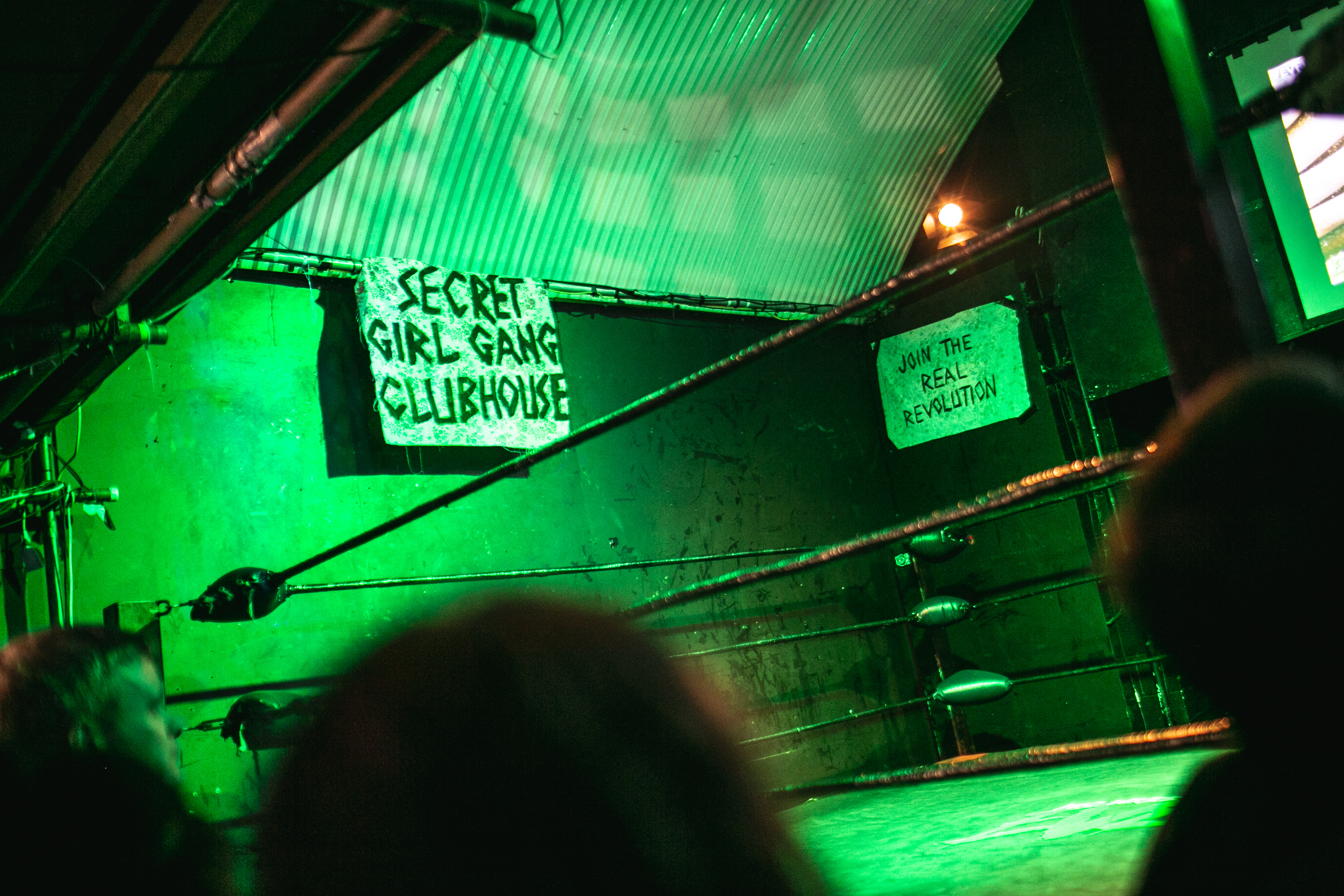 "A ""secret girl gang"" sign hangs above the Eve wrestling ring"