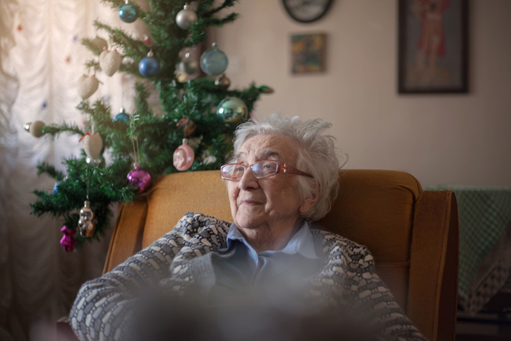 dementia patient at Christmas sat by tree