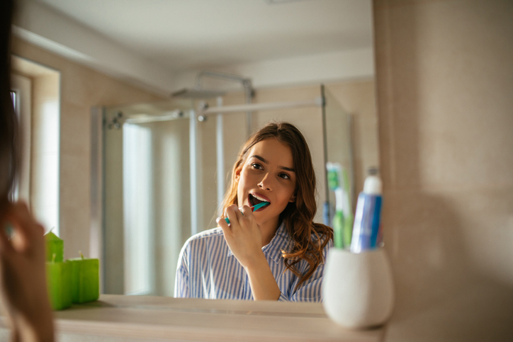 a couple brushing their teeth to take care of their hearing