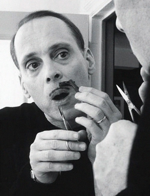 John Waters drawing on his moustache