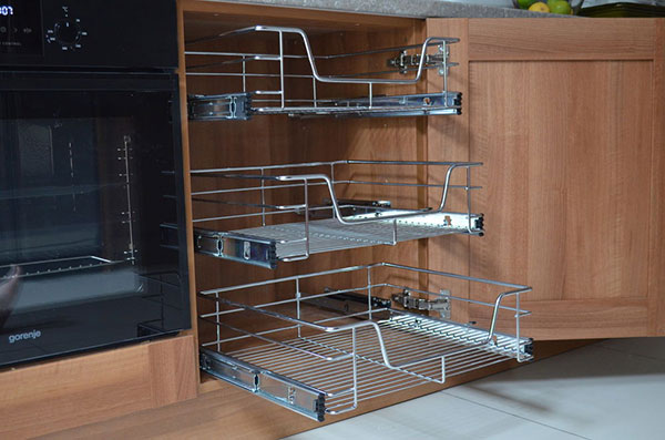 Wire baskets in kitchen cupboard for storage