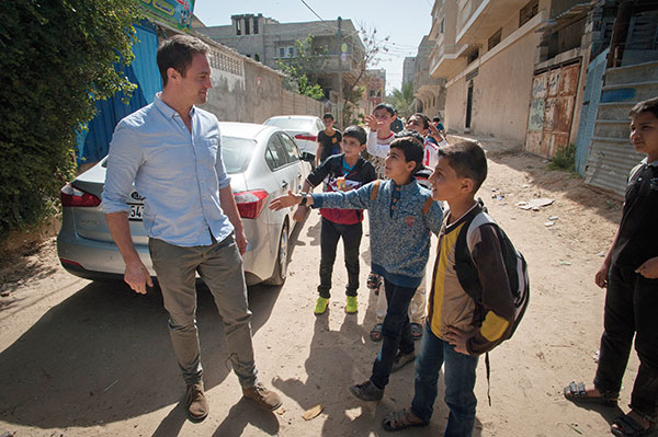 Sam is greeted by Palestinian children as he enters a community centre