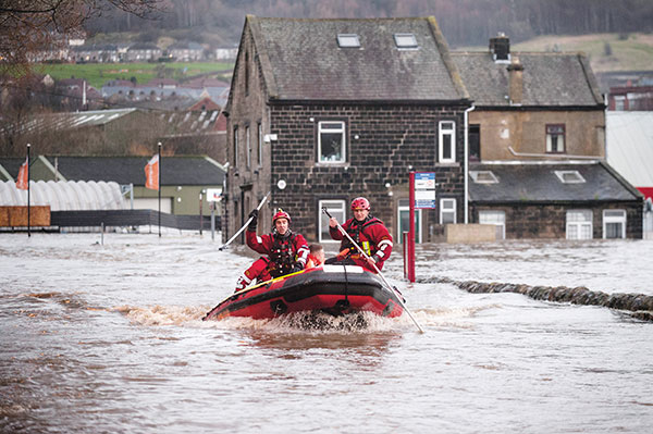 Firefighters rescuing people from the floods in cumbria