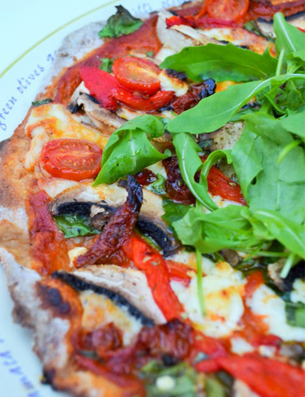 Homemade mediterranean pizza with goats cheese and rocket